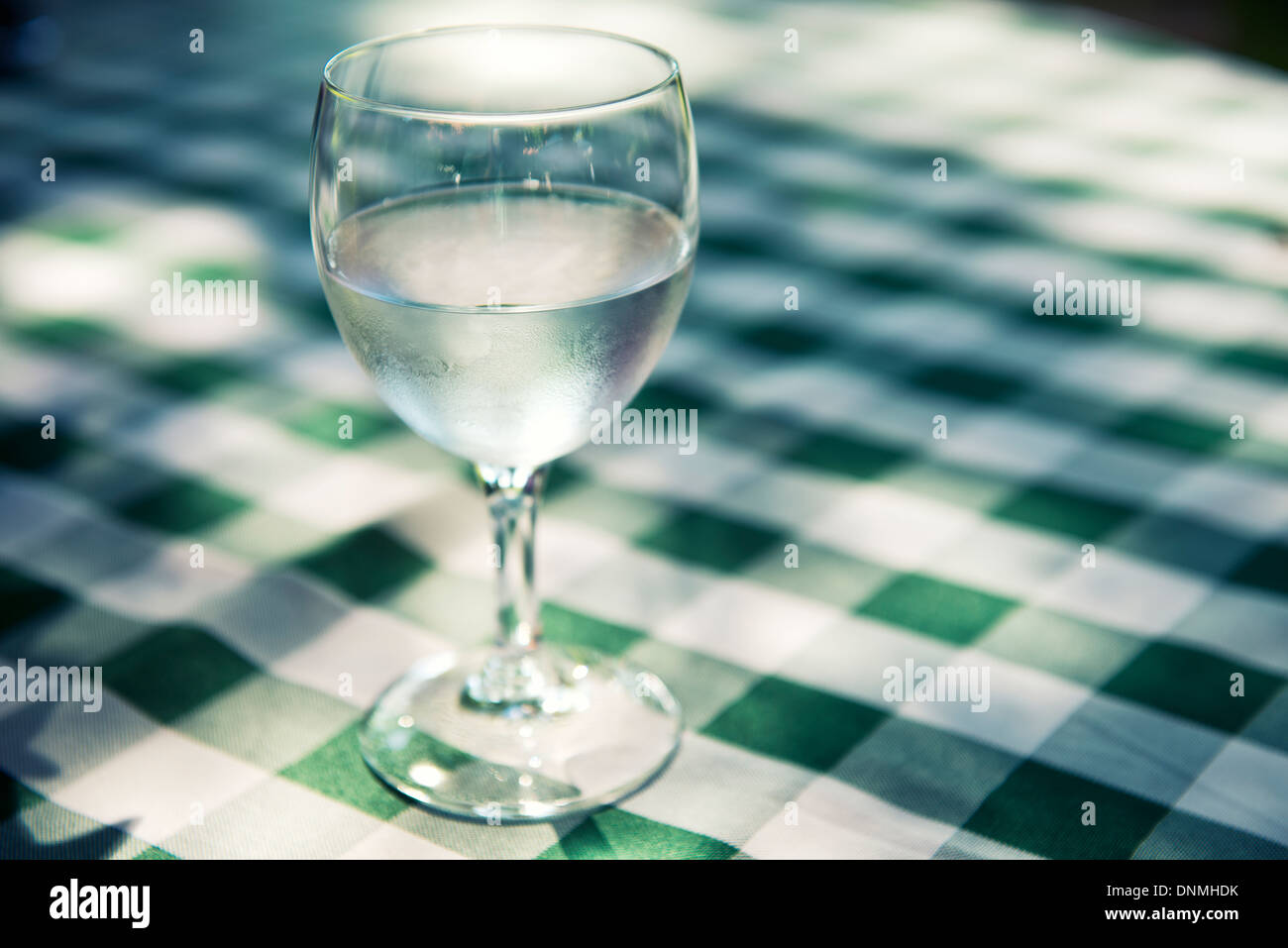 Glass of fresh water on table with green checkered tablecloth - Stock Image