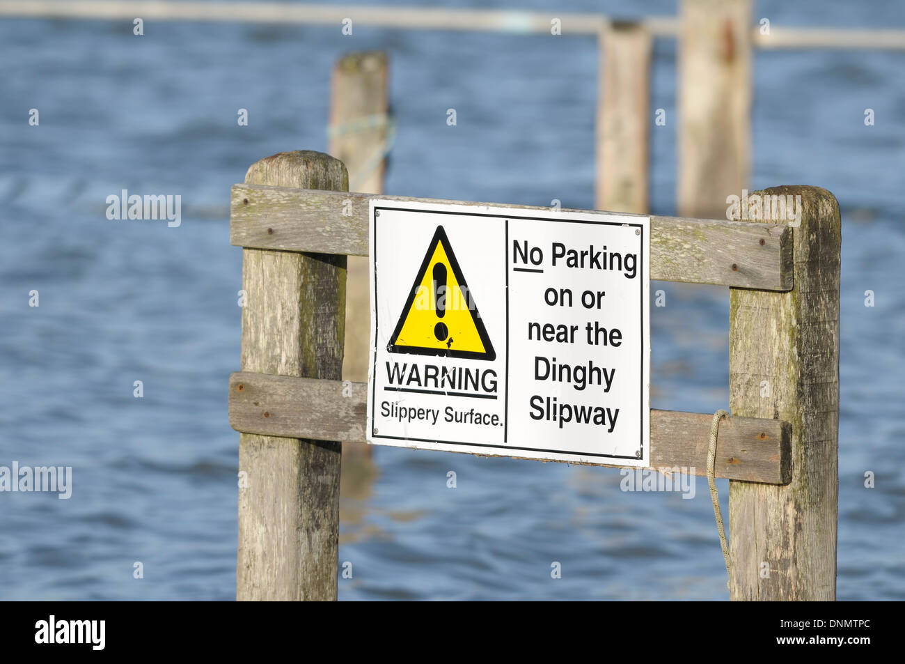 warning sign showing slippery surface and no parking on or near the dingy slipway at bosham west sussex UK - Stock Image