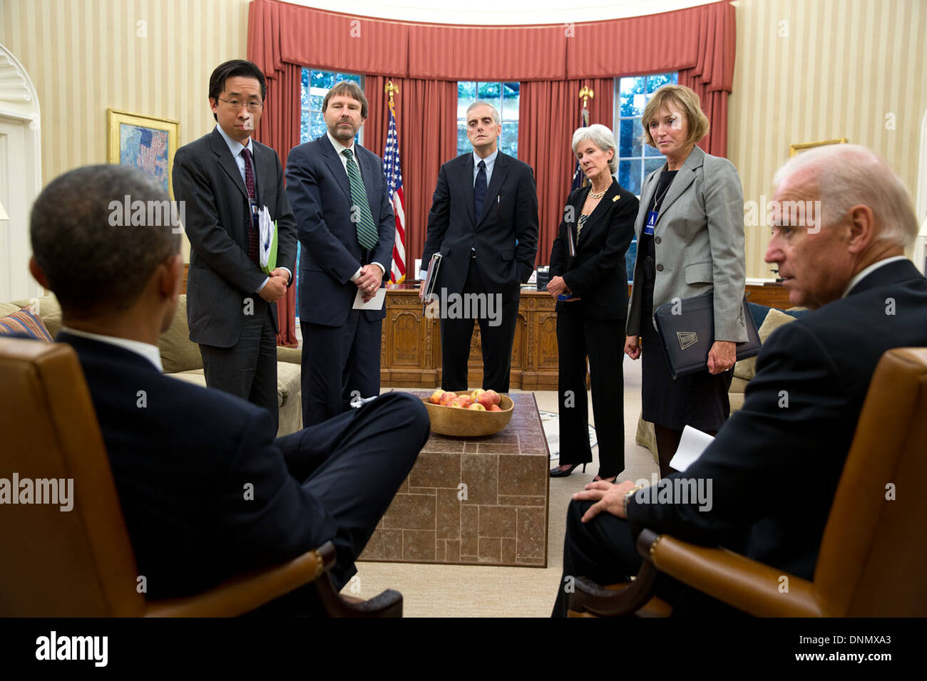 US President Barack Obama talks with staff at the conclusion of a meeting to discuss the problems associated with enrollment in the Affordable Care Act in the Oval Office of the White House October 10, 2013 in Washington, DC. - Stock Image