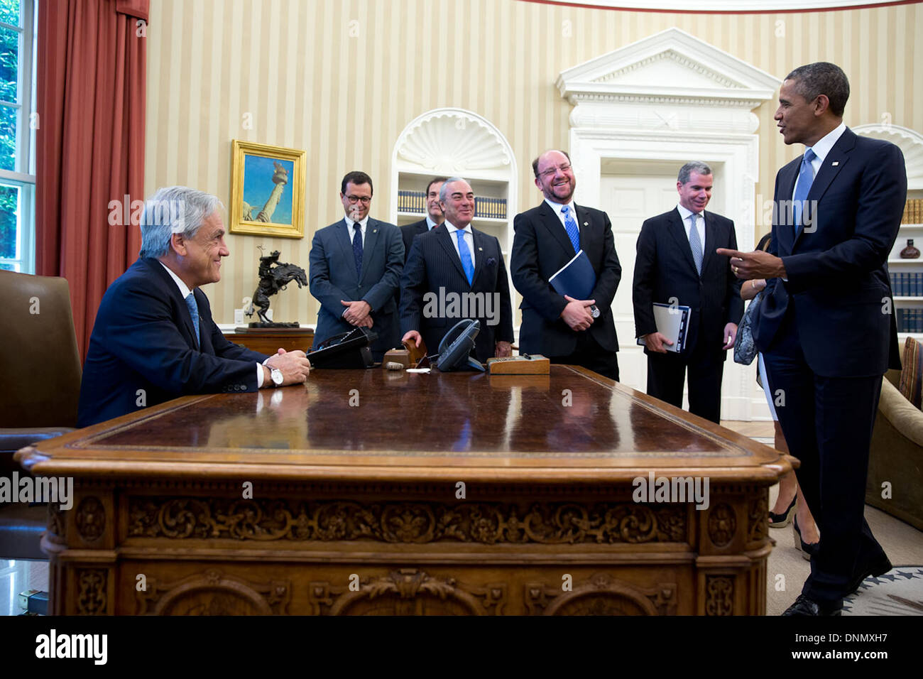 US President Barack Obama jokes with President of Chile Sebastion Pinera as he sits at the Resolute Desk in the Oval Office of the White House June 4, 2013 in Washington, DC. - Stock Image