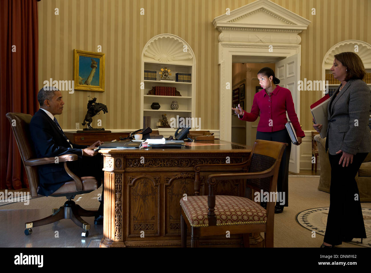 US President Barack Obama talks with advisors Susan Rice and Lisa Monaco before his phone call with Chancellor Angela Merkel of Germany to discuss the latest NSA leak from Edward Snowden in the Oval Office of the White House October 23, 2013 in Washington, DC. - Stock Image