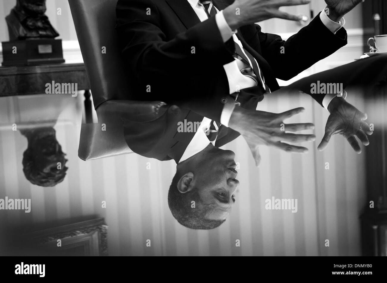US President Barack Obama is reflected in a glass table top during a meeting in the Oval Office of the White House Stock Photo