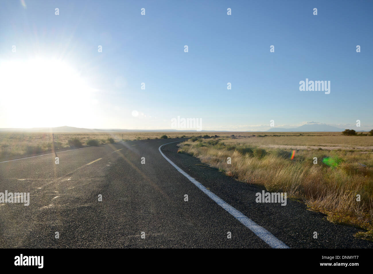 Low sun over desert road bend, Arizona, USA. Route 66 background - Stock Image