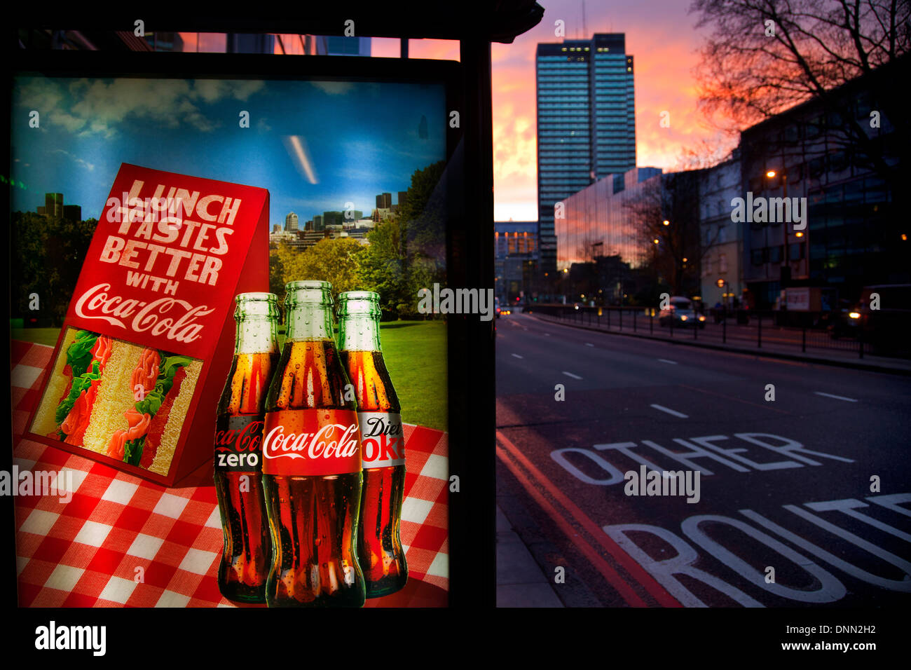 Coca-Cola advertising sign on bus stop at dusk, Warren Street, London - Stock Image