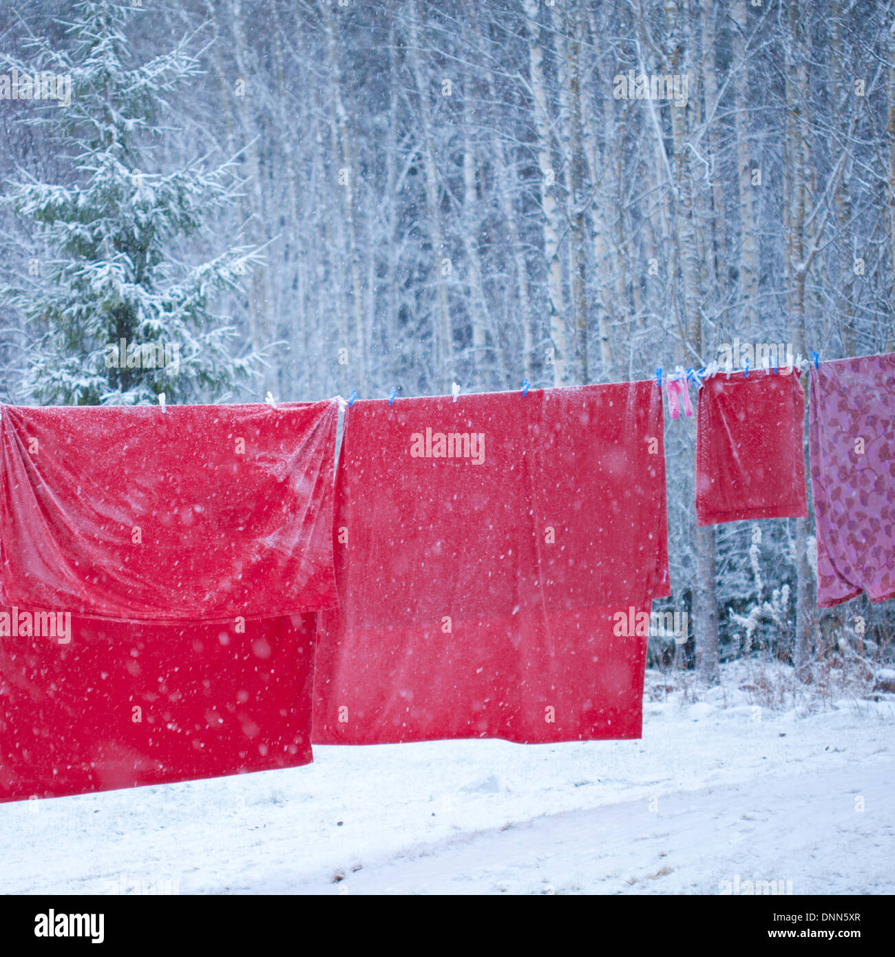 Santa bedlinen drying on clothesline in the snow - Stock Image