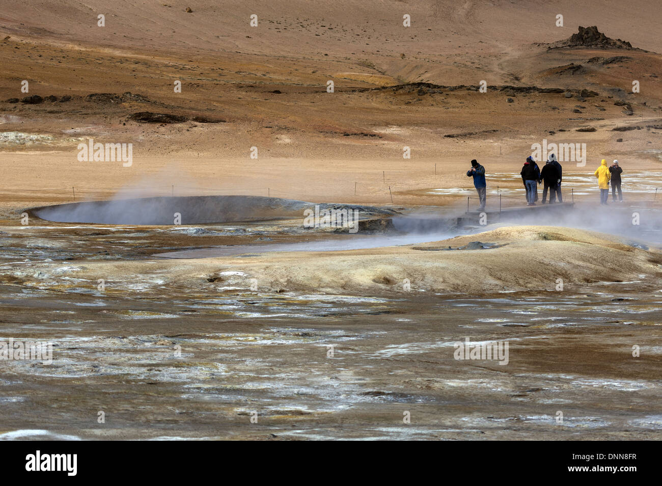 Tourists on the Hverarond geothermal hot spring area examining the steaming and bubbling mud pools, north east Iceland - Stock Image