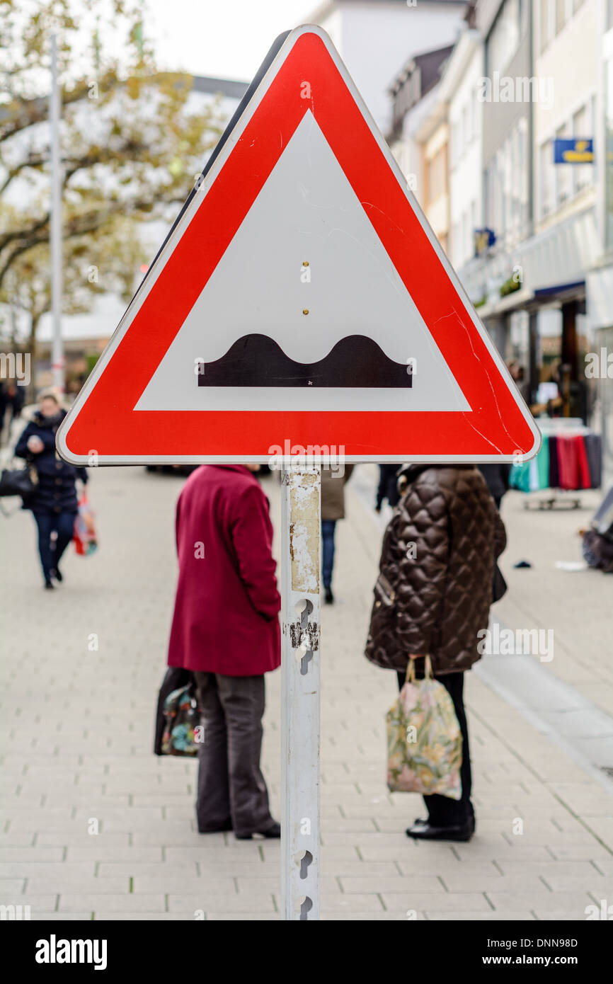 """Two women wearing winter coats, carrying plastic shopping bags, standing behind a """"Uneven Road"""" traffic sign - Stock Image"""