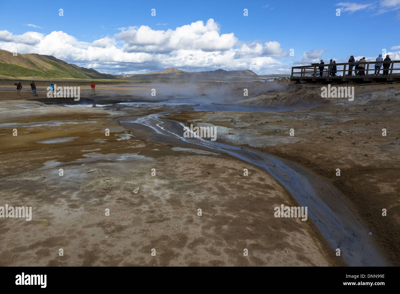 Iceland Tourists at the Namafjall geothermal hot spring area examining the steaming and bubbling pools - Stock Image