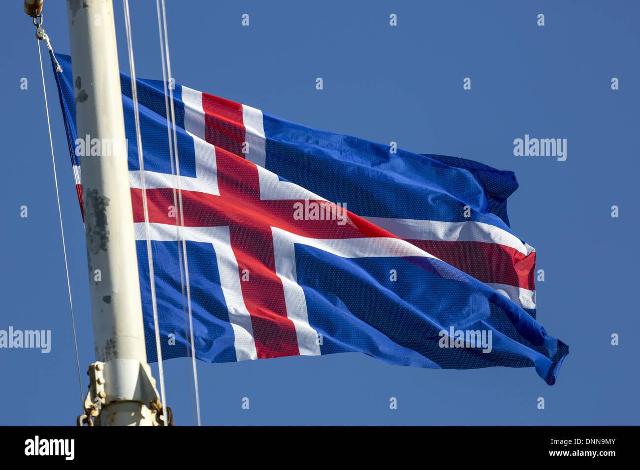 Icelandic Flag flying in bright sunshine from a flag pole - Stock Image