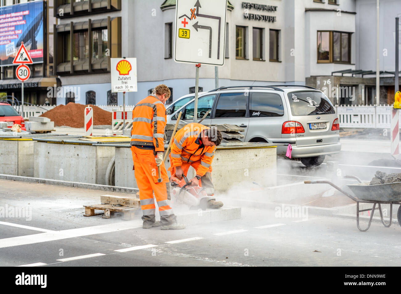 Two roadworkers in orange signal coloured workwear, one man with hammer, one man cutting a stone block with a angle grinder - Stock Image