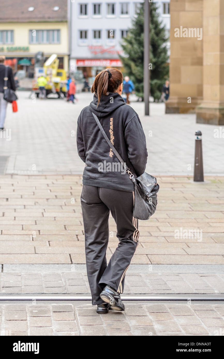 Young Caucasian woman with brown hair done in a ponytail dressed in black Adidas sports suit crosses a street with embeded rails - Stock Image