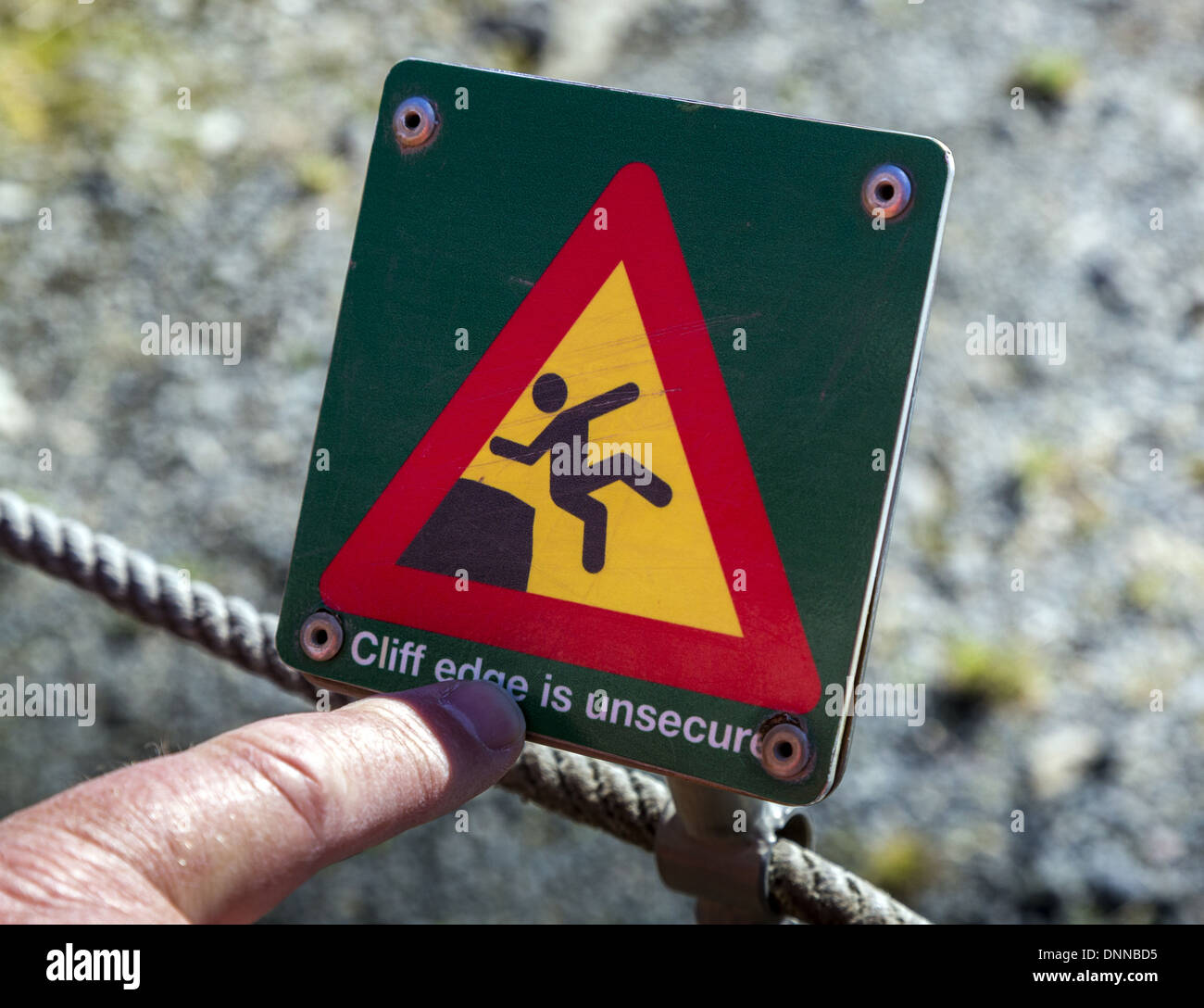 Finger pointing at red and yellow danger sign with diagram of person sliiping or falling indicating the risk of falling Iceland - Stock Image