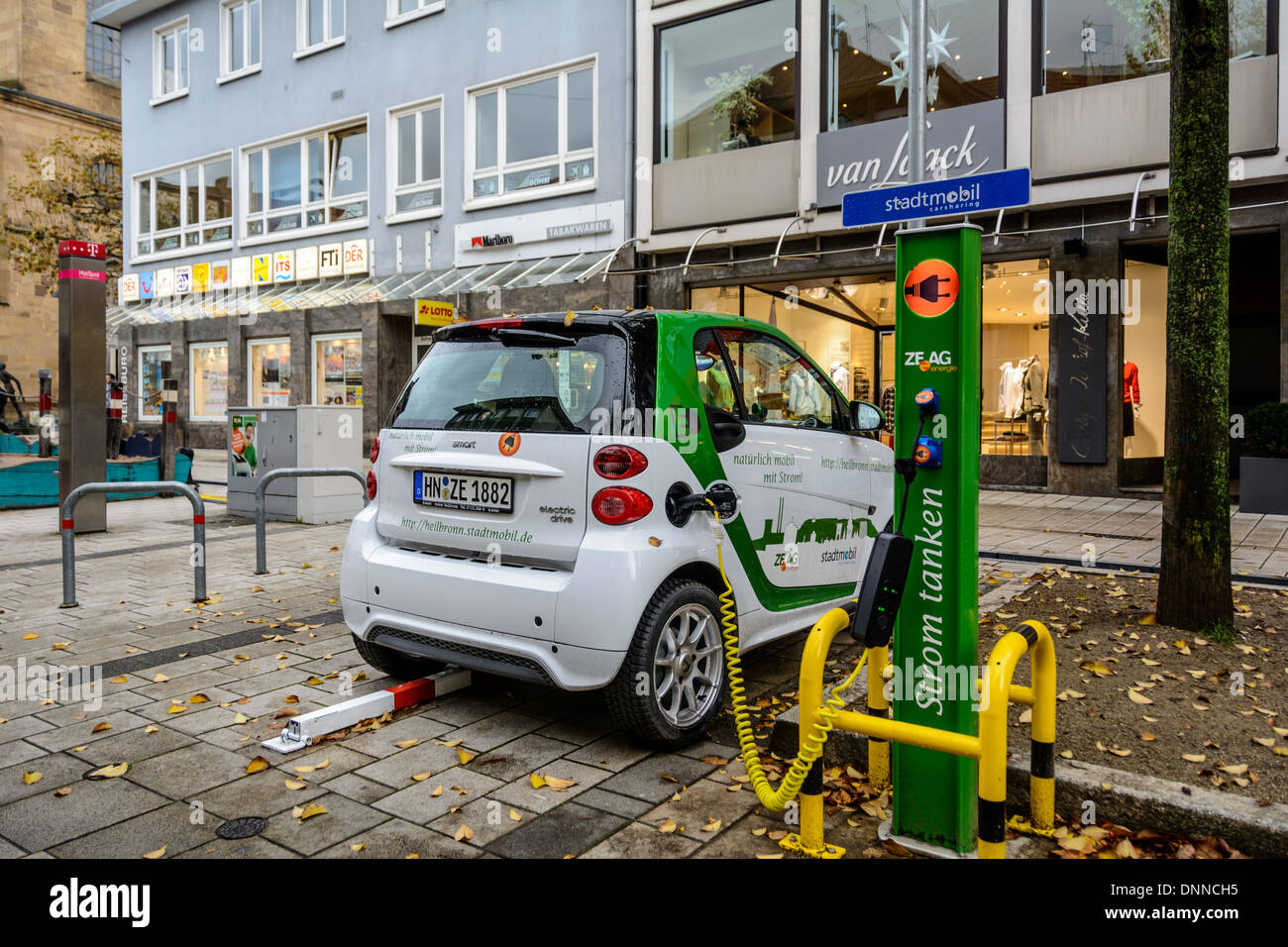 Smart electric drive electrically powered compact car charging the battery on an electric vehicle charging station, Stock Photo