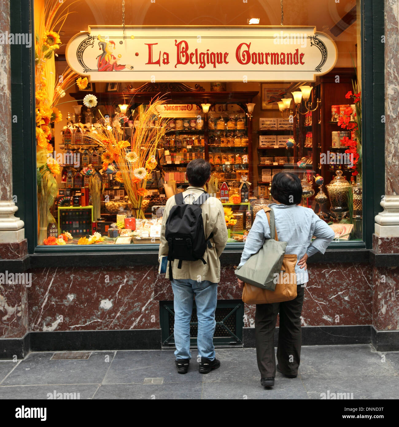 Tourists looks at a Belgian gourmet shop in the Galeries Royales Saint-Hubert shopping gallery in Brussels, Belgium. - Stock Image