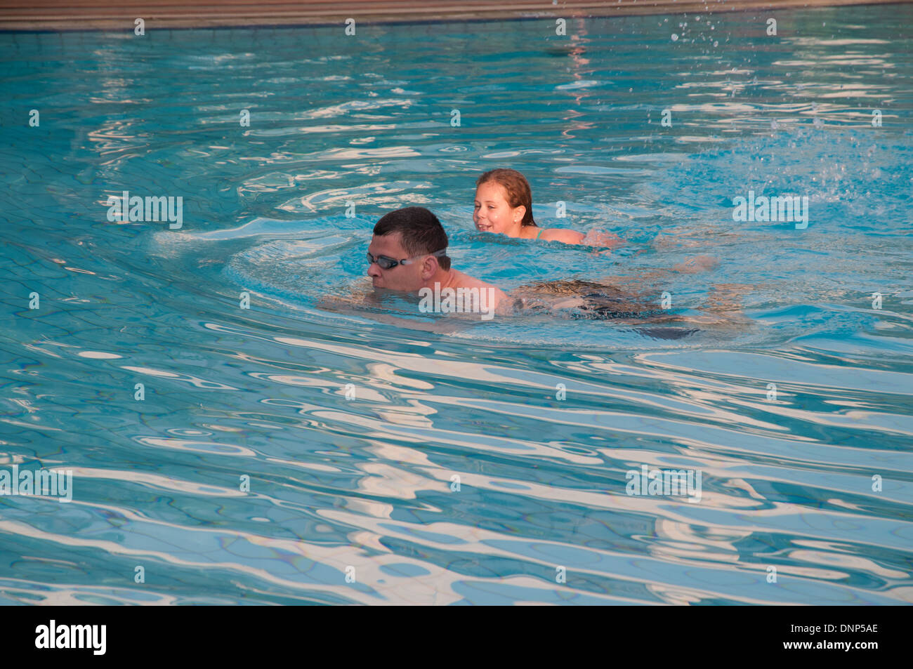Two swimmers a father and daughter in the swimming pool of Nairobi Serena Hotel Kenya - Stock Image