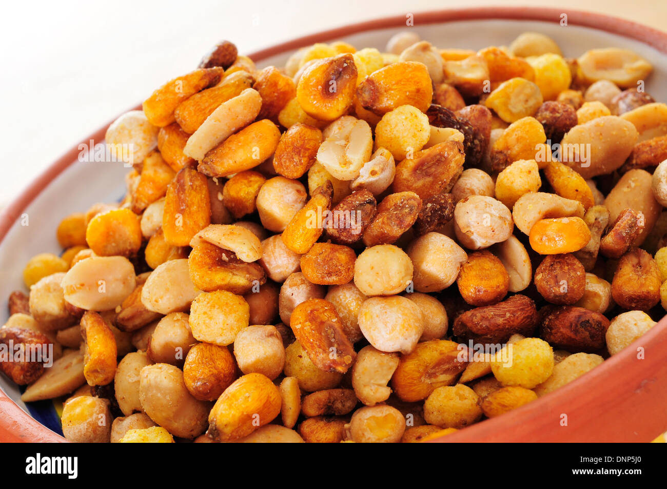 a bowl with mixed nuts, such as roasted and salted peanuts, corn or chickpeas - Stock Image