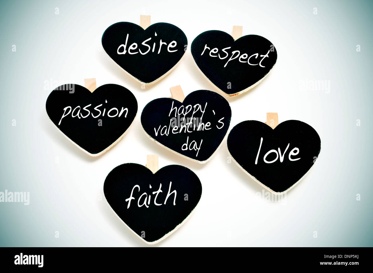 some heart-shaped blackboards with different words written on them related to love concept, such as respect or passion, and the - Stock Image