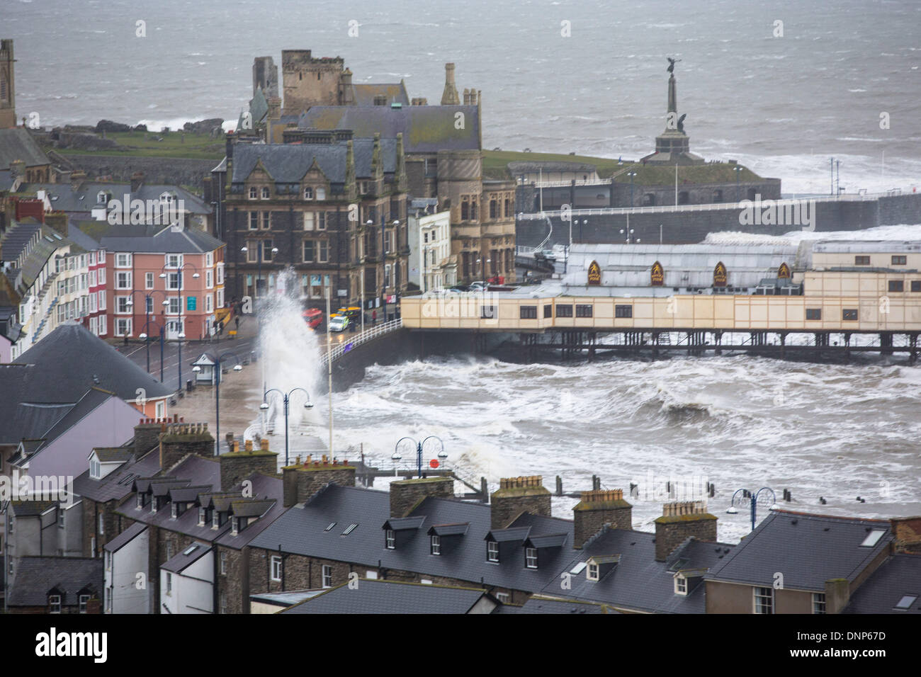 Aberystwyth, mid Wales, UK. 3 January 2014. Strong winds and a spring tide cause waves to batter the west Wales coast. The promenade at Aberystwyth was closed to the public as waves tore over the sea wall, breaking sea defences and spreading debris over a wide area. Police and coastguards cordoned-off the north and south promenades at high tide, and a fire engine became stranded. Credit:  atgof.co/Alamy Live News - Stock Image