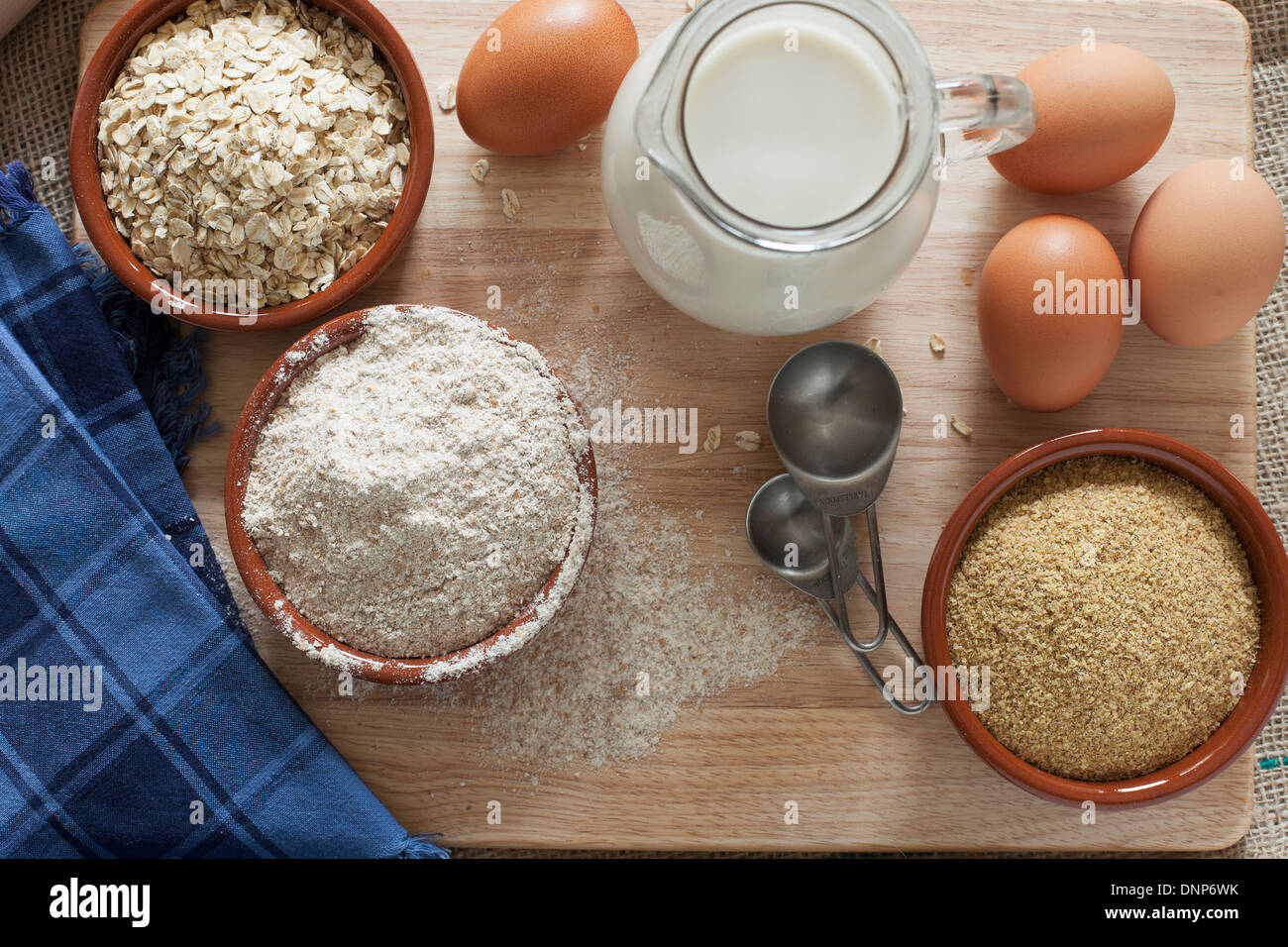 Ingredients for whole grain healthy bread, whole wheat flour, rolled oats and wheat germ with milk and eggs. - Stock Image