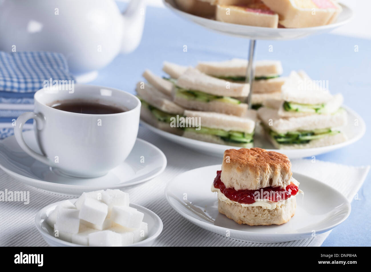 Cup of tea with sugar cubes and scones, cucumber sandwiches in the background - Stock Image