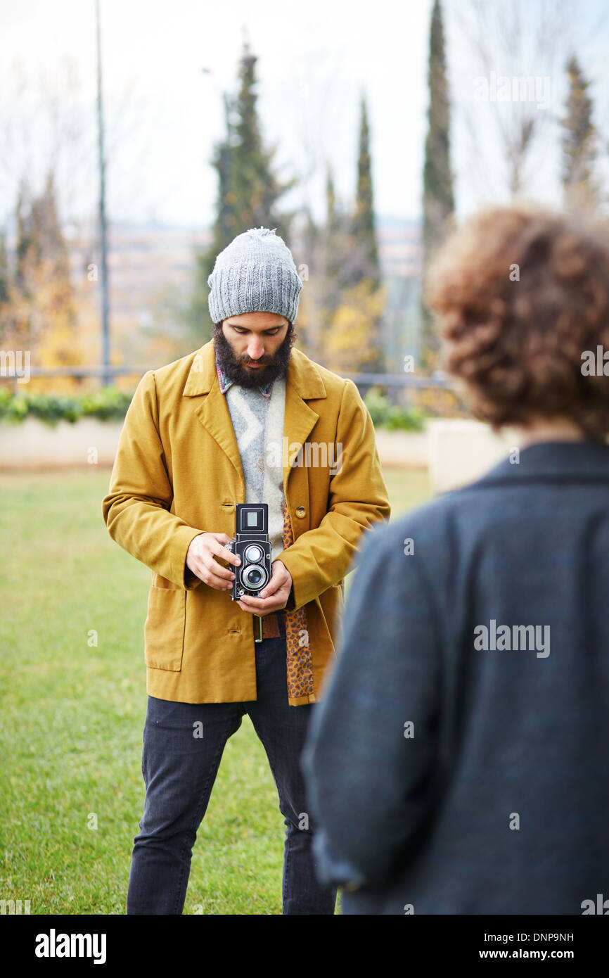 Young bearded hipster taking photo to redhead girl with TLR camera outdoors - Stock Image