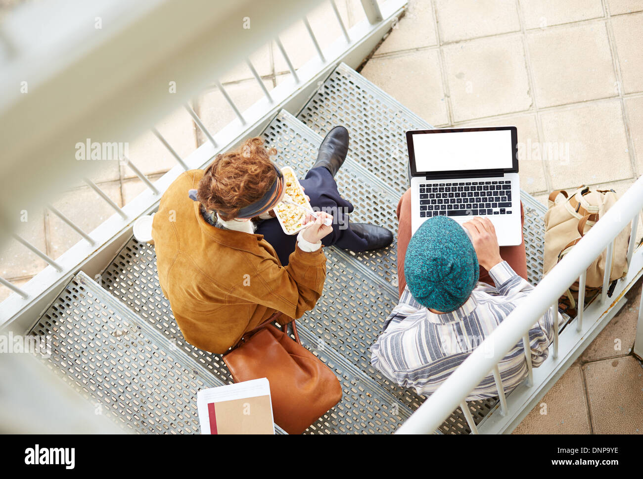 Hipster couple using computer and eating lunch sitting in stairs at university campus - Stock Image
