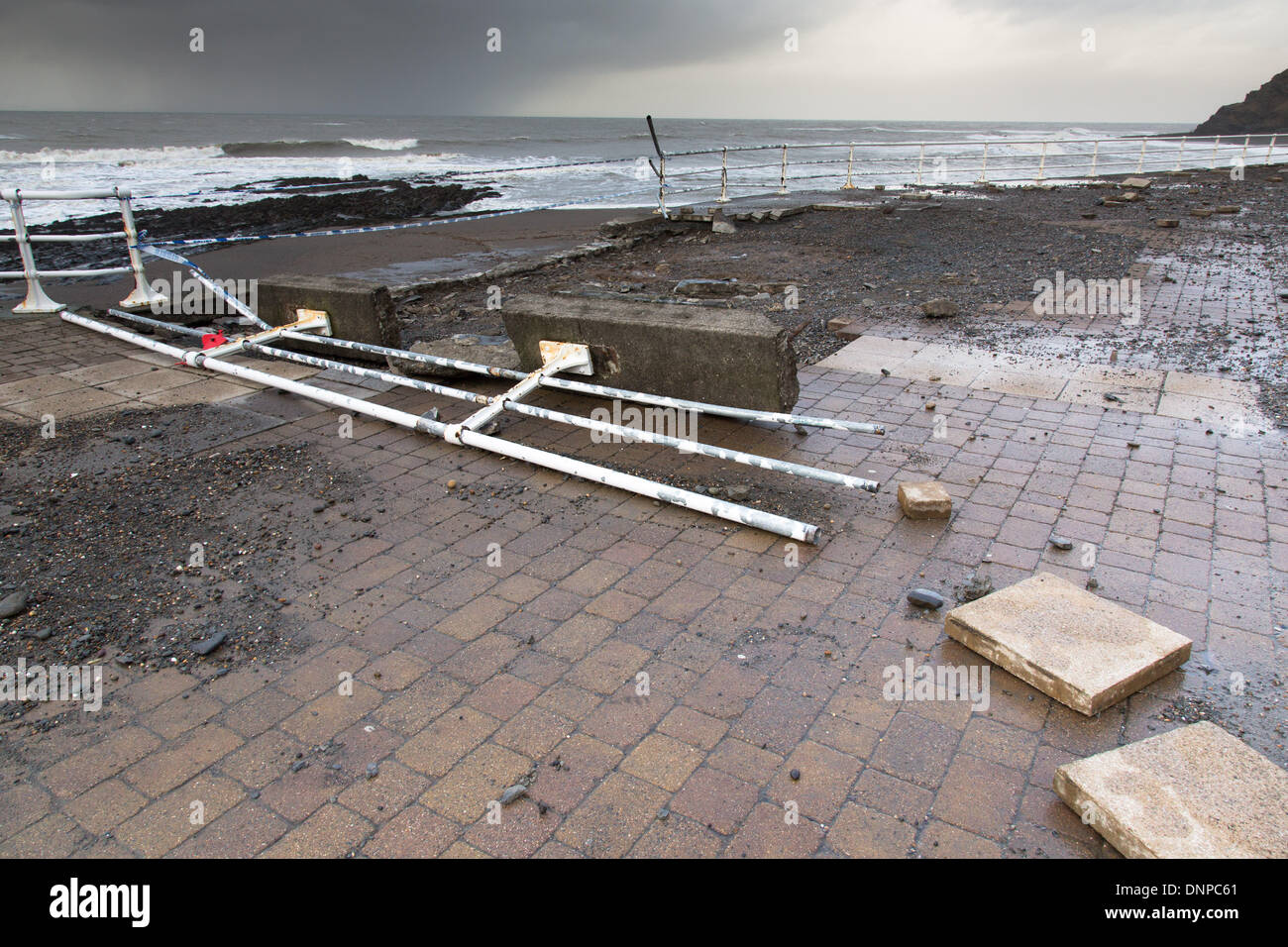 Aberystwyth, UK. 03rd Jan, 2014. Damage on Aberystwyth seafront. Strong winds and a spring tide caused waves to batter the west Wales coast. The promenade at Aberystwyth was closed to the public as waves tore over the sea wall, breaking sea defences and spreading debris over a wide area. Police and coastguards cordoned-off the north and south promenades at high tide, and a fire engine became stranded. Credit:  atgof.co/Alamy Live News - Stock Image