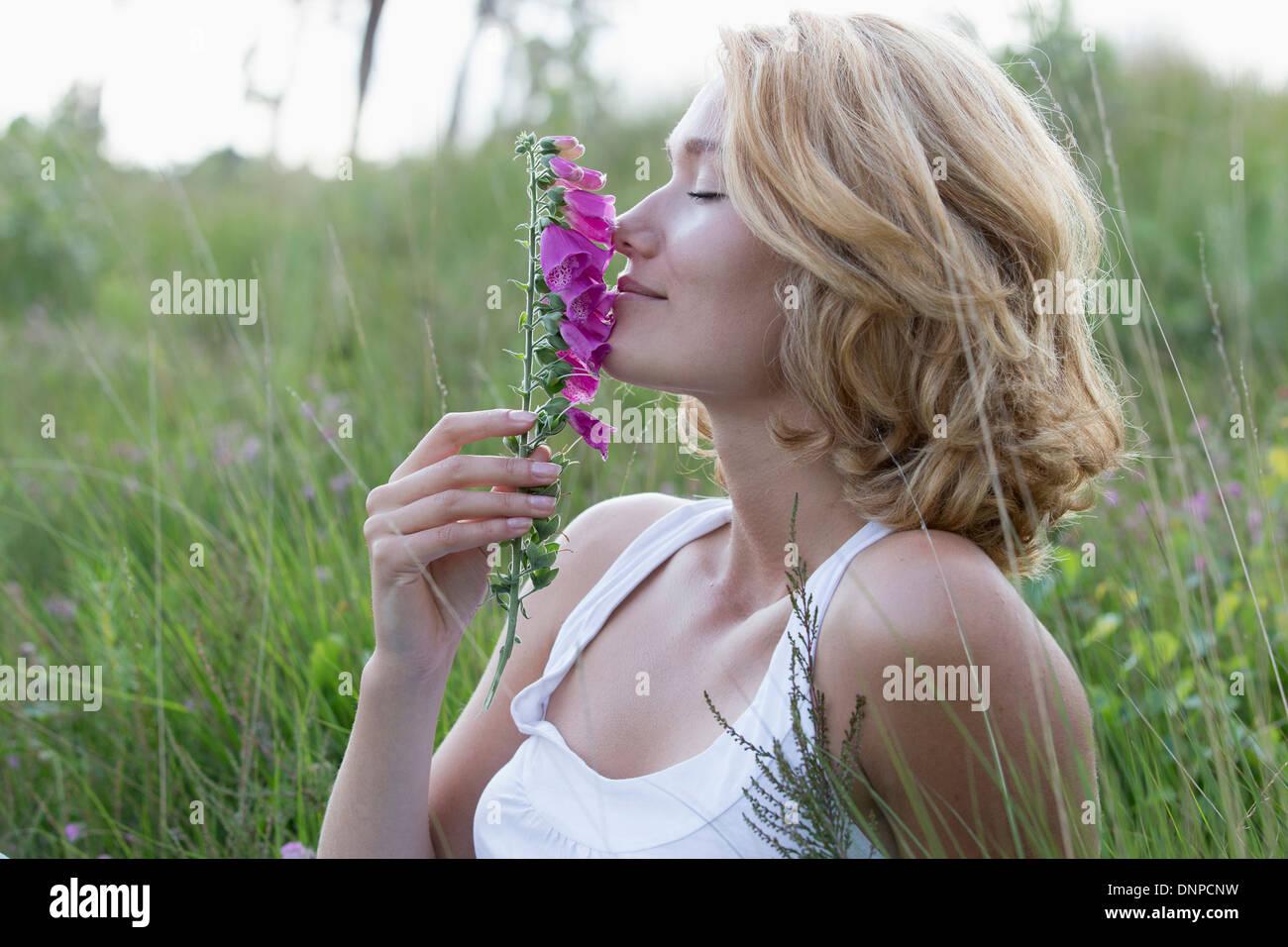 Netherlands, Gelderland, Hatertse Vennen, Portrait of happy woman with purple flower Stock Photo