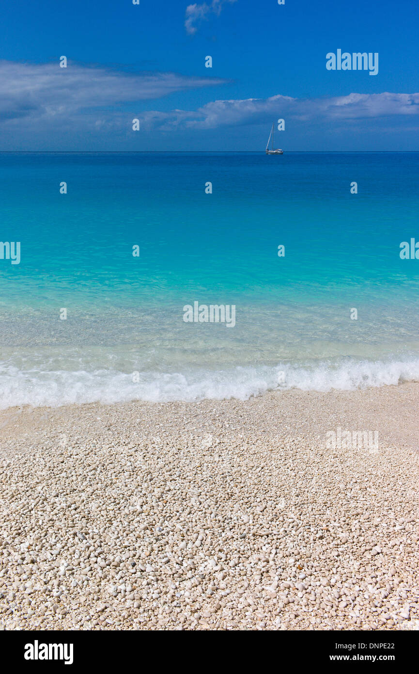 Turquoise blue sea with waves, white pebbles and yacht at Myrtos Beach, Cefalonia, Greece - Stock Image