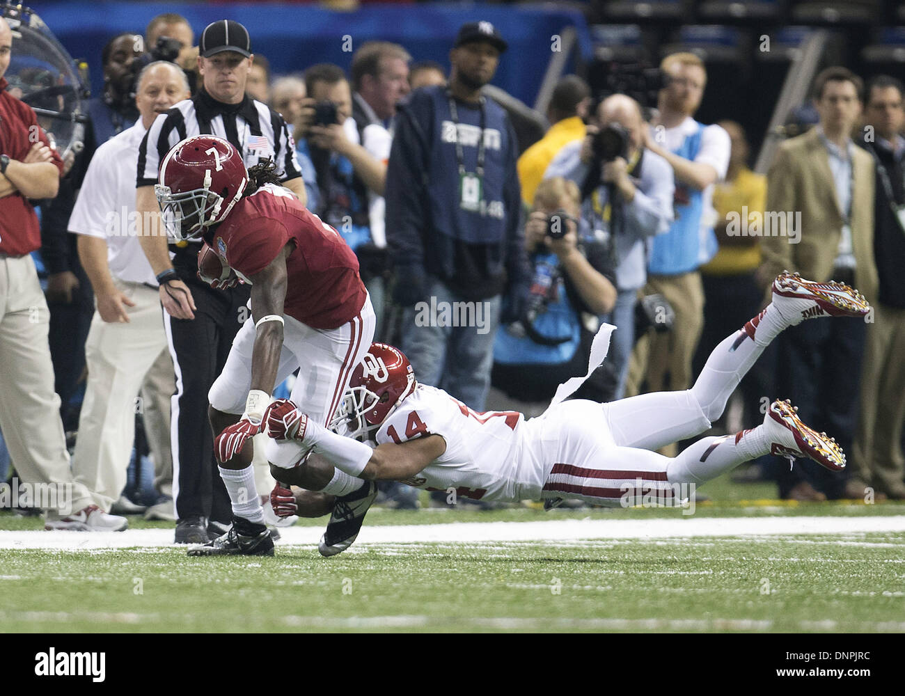 New Orleans, Louisiana, USA. 2nd Jan, 2014. January 02, 2014: Alabama wide receiver Kenny Bell (7) runs for yardage as Oklahoma defensive back Aaron Colvin (14) attempts to make the tackle during NCAA Football game action between the Oklahoma Sooners and the Alabama Crimson Tide at Mercedes-Benz Superdome in New Orleans, Louisiana. Oklahoma defeated Alabama 45-31. Credit:  csm/Alamy Live News - Stock Image