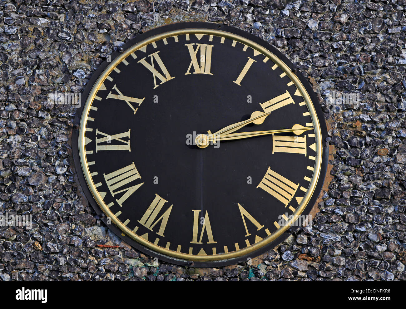 Circular black clock with gold roman numerals attached to a flint wall - Stock Image