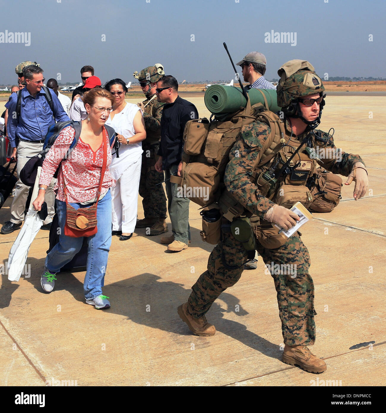 A US Marine from the Crisis Response team guides American citizens to an evacuation flight January 3, 2014 in Juba, South Sudan. The Marines evacuated more than 20 personnel from the U.S. Embassy as conflict escalates in South Sudan following a failed coup attempt. - Stock Image