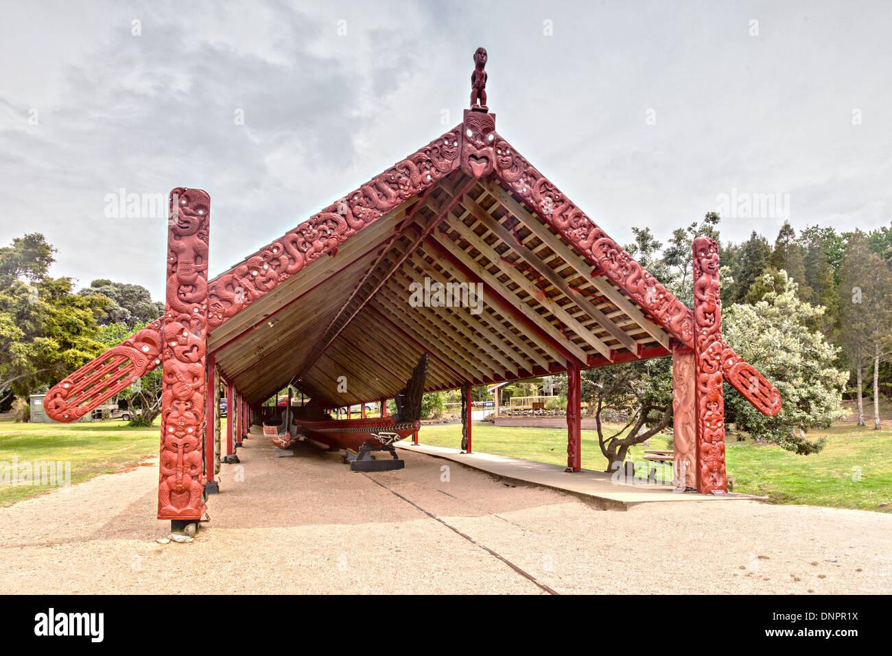 The traditionally styled boathouse on the Waitangi Treaty Grounds, Northland, New Zealand, houses two waka (canoes), ... - Stock Image