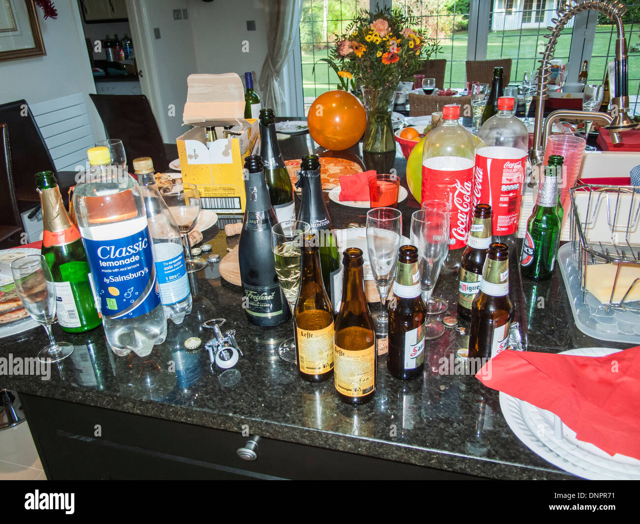 Messy, untidy kitchen after a party: empty wine, beer & drink glass bottles, plastic bottles, dirty paper plates, unwashed champagne glasses as trash - Stock Image