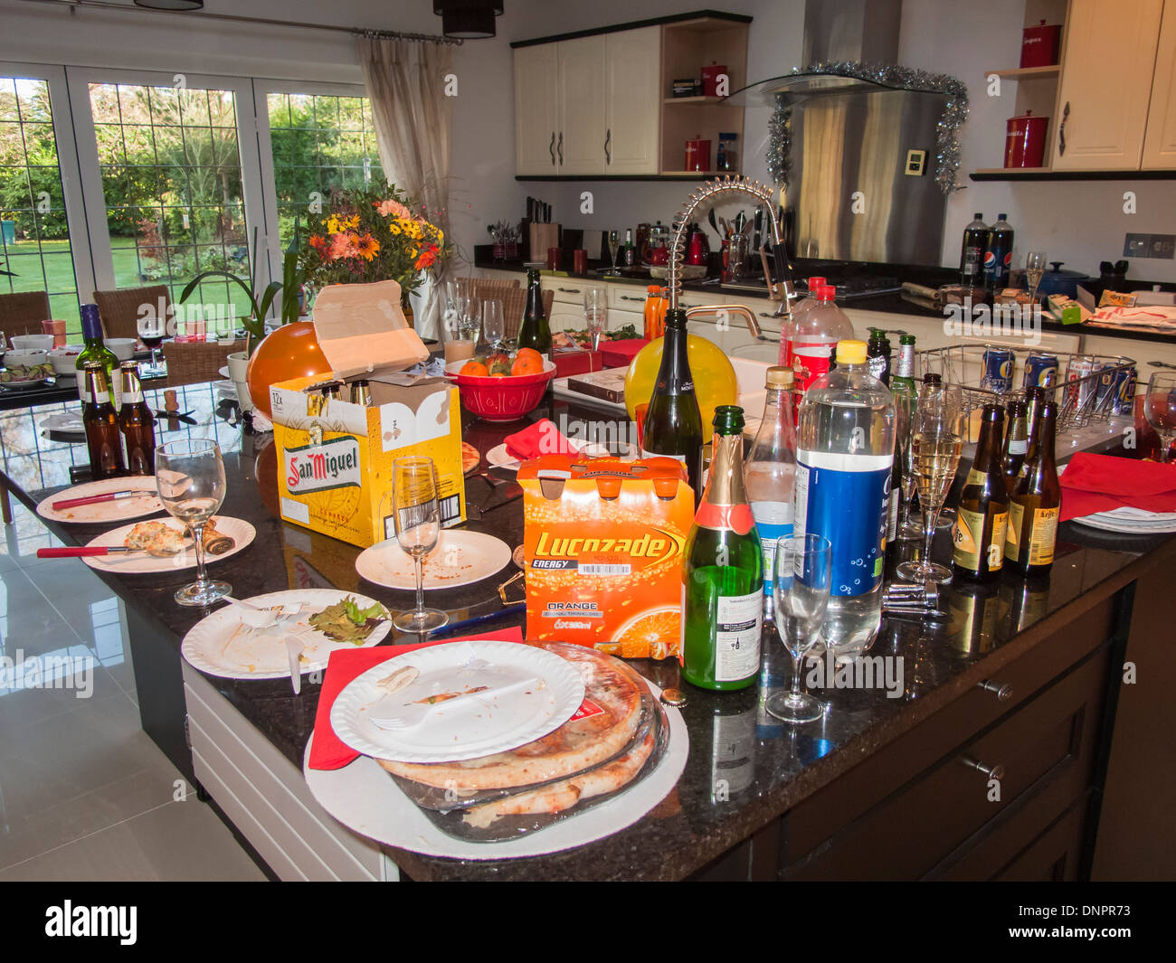 Messy, untidy kitchen after a party - empty wine & beer bottles, dirty paper plates, left-over food, unwashed champagne glasses - Stock Image