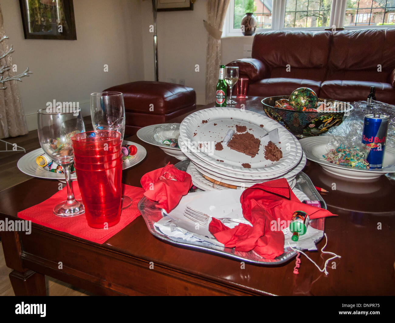 Mess after a festive season party - dirty paper plates, plastic cups, discarded napkins, empty glasses, drink can and bottle - Stock Image
