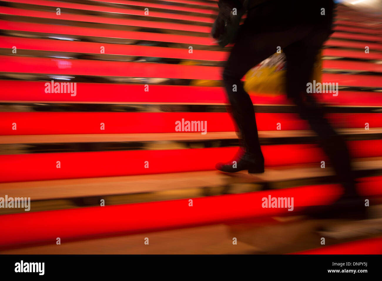 Shopper Walking Up Lighted Stairs - Stock Image