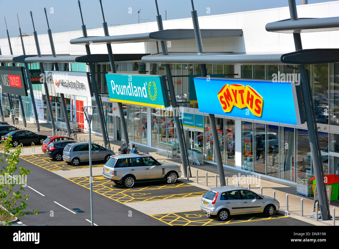 Free disabled parking bays outside retail park shopping units including Smyths, Poundland, Nike, and M&S Outlet stores - Stock Image