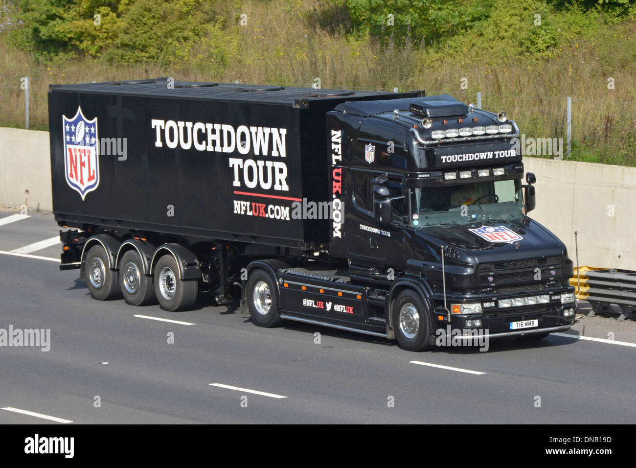 Scania truck and trailer promoting the NFL Touchdown Tour driving along the M25 motorway - Stock Image