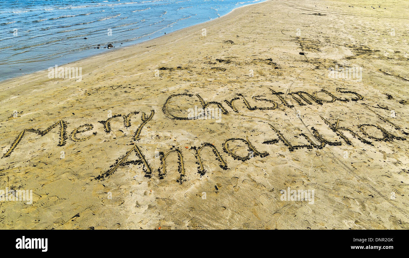 Christmas wishes written into the sand of Phinikoudes Beach Larnaca, Cyprus. - Stock Image