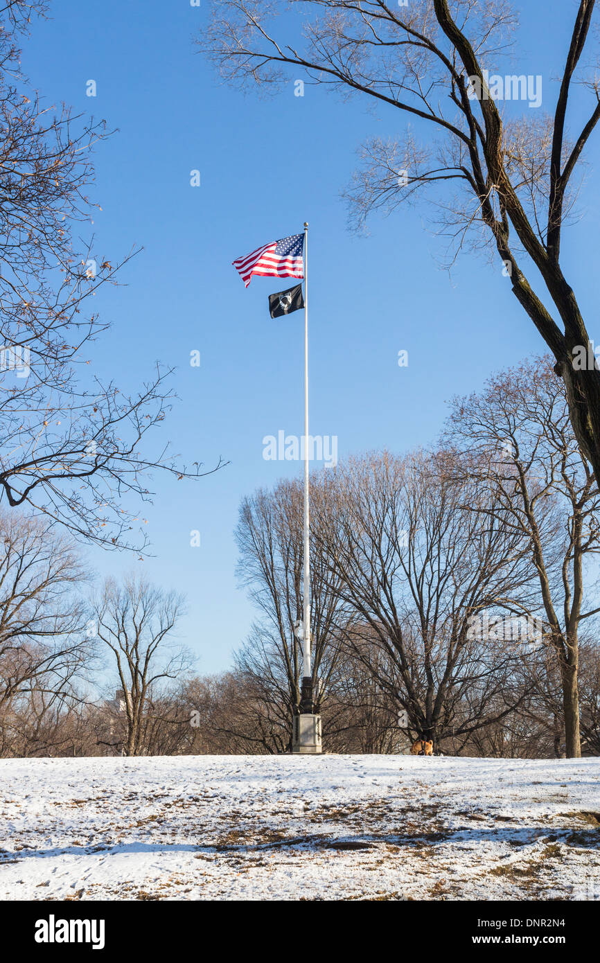 American Stars & Stripes national flag flying from flagpole in Central Park, New York against a blue sky with snow on ground - Stock Image