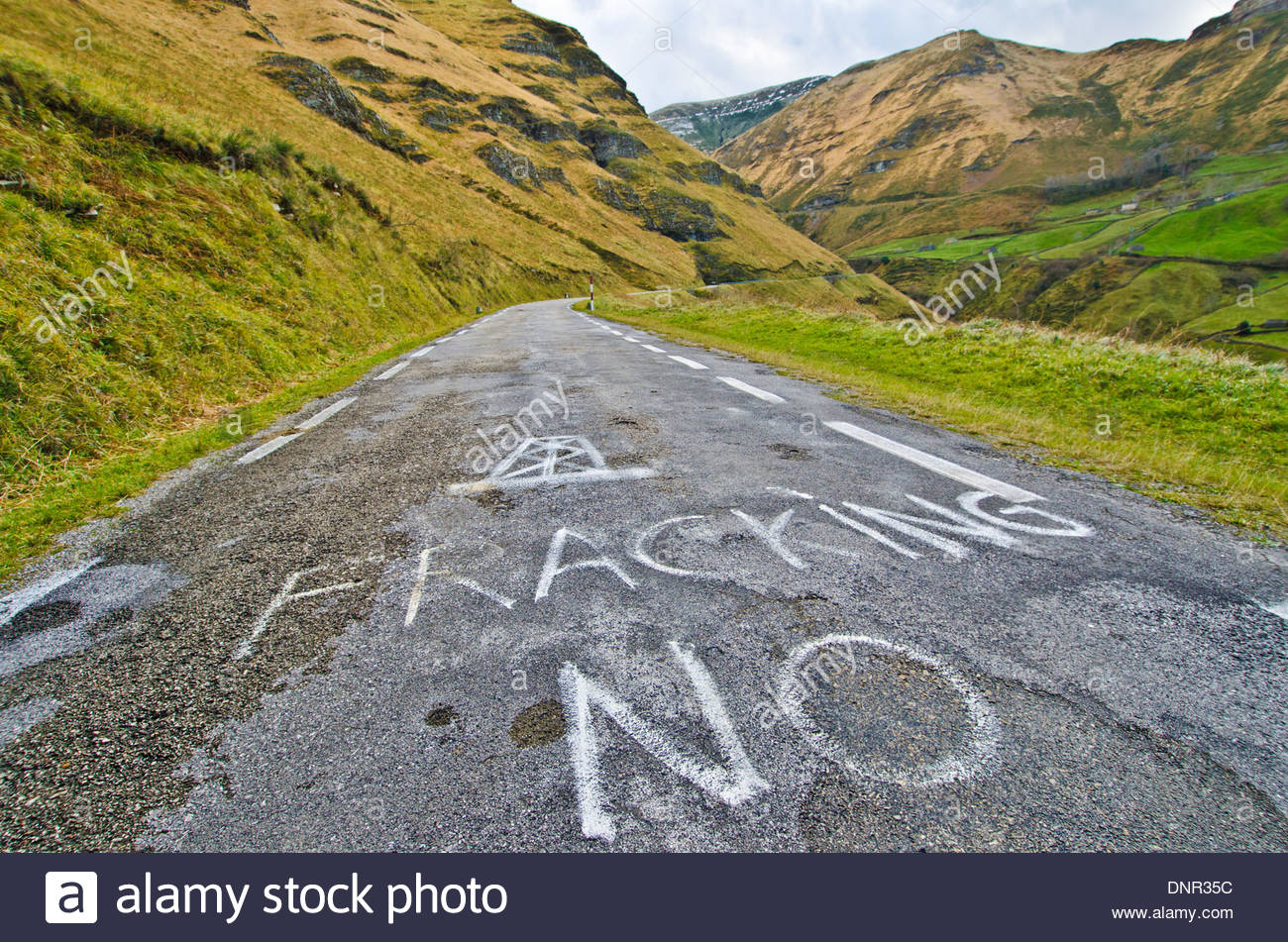 Anti-fracking slogan 'No to fracking' spraypainted on a mountain road in the Cantabrian mountains near the - Stock Image