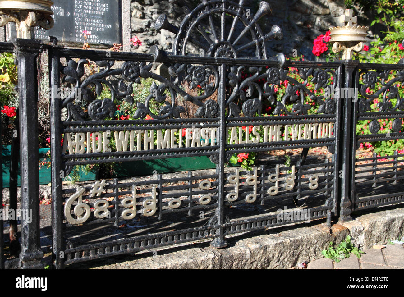 A war memorial with wrought iron gates inscribed 'Abide with Me Fast falls the Eventide'. - Stock Image