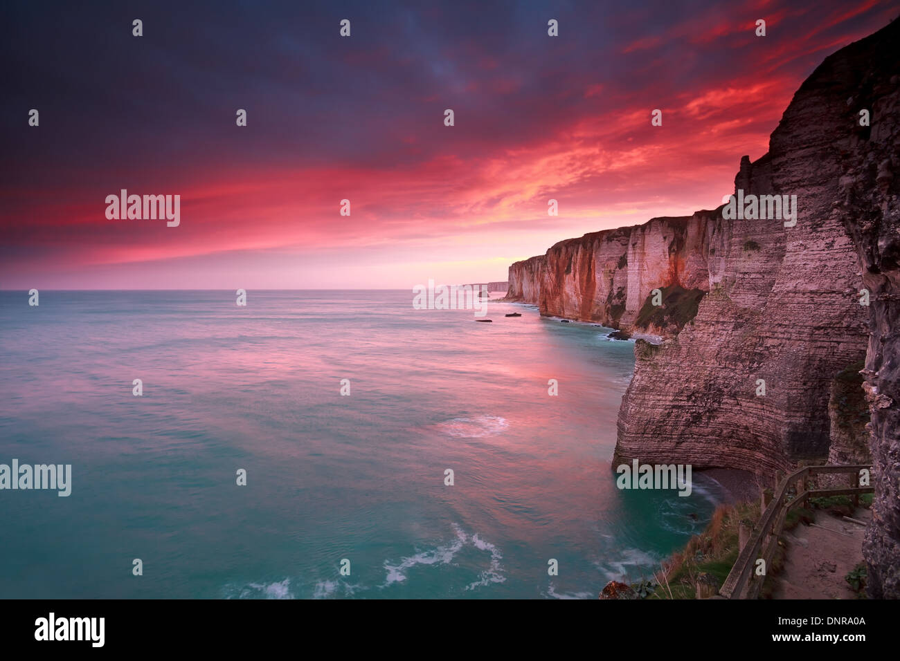dramatic sunrise over ocean and cliffs, Etretat, France - Stock Image