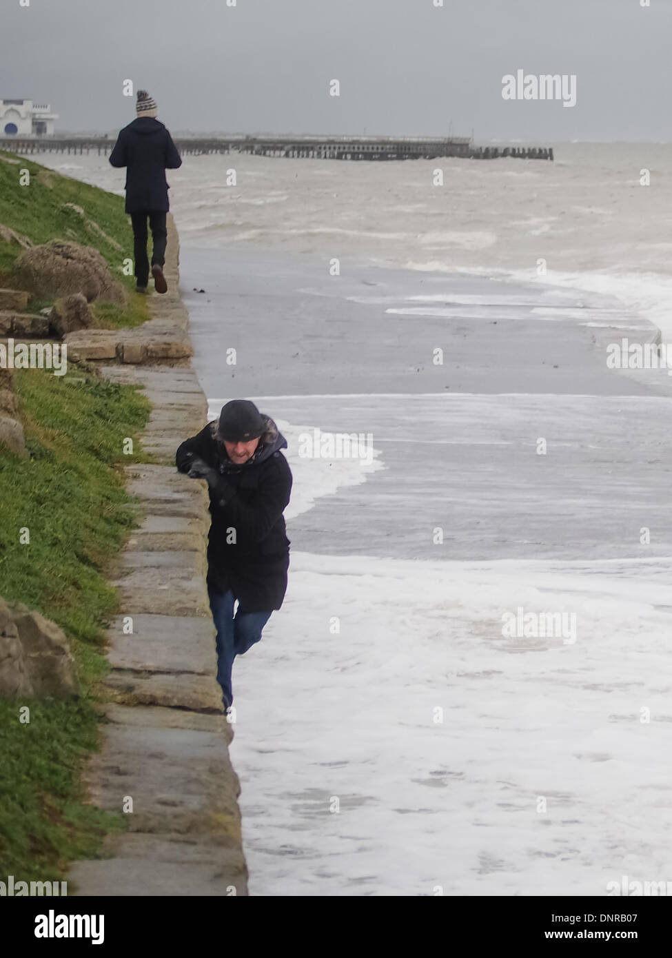 Portsmouth, England 4th January 2014. A man climbs onto  a wall beside a coastal footpath as a wave washes over the path below him. The UK has experienced a period of exceptionally high tides and large waves causing flooding in many coastal areas. Credit:  simon evans/Alamy Live News - Stock Image