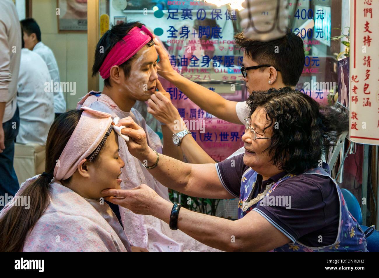 Facial Threading, a Chinese Traditional Facial Technique in Taipei Raohe Street Night Market, Taipei, Taiwan - Stock Image