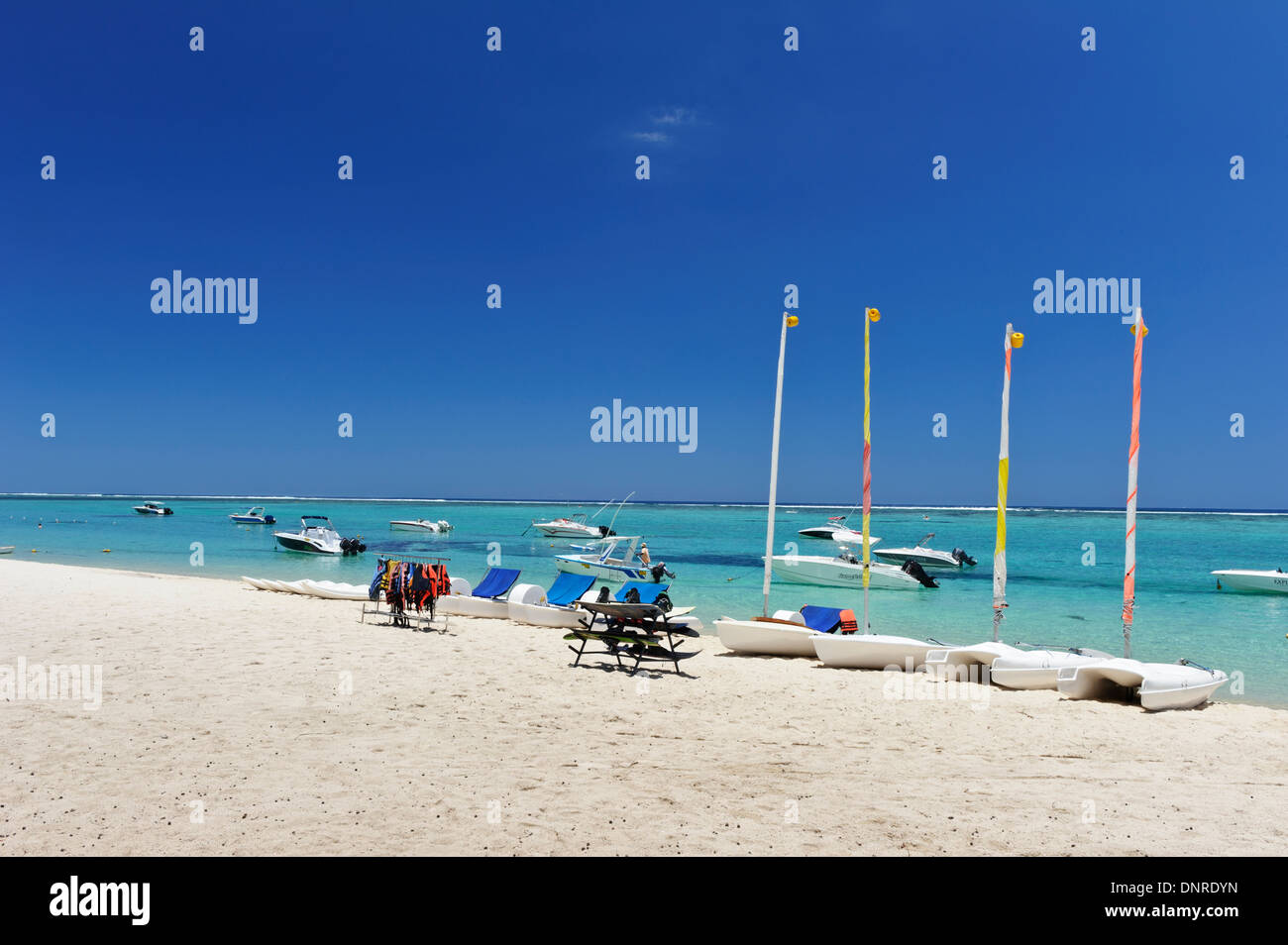 Water sport equipment on sandy beach and turquoise sea of Mauritius. - Stock Image