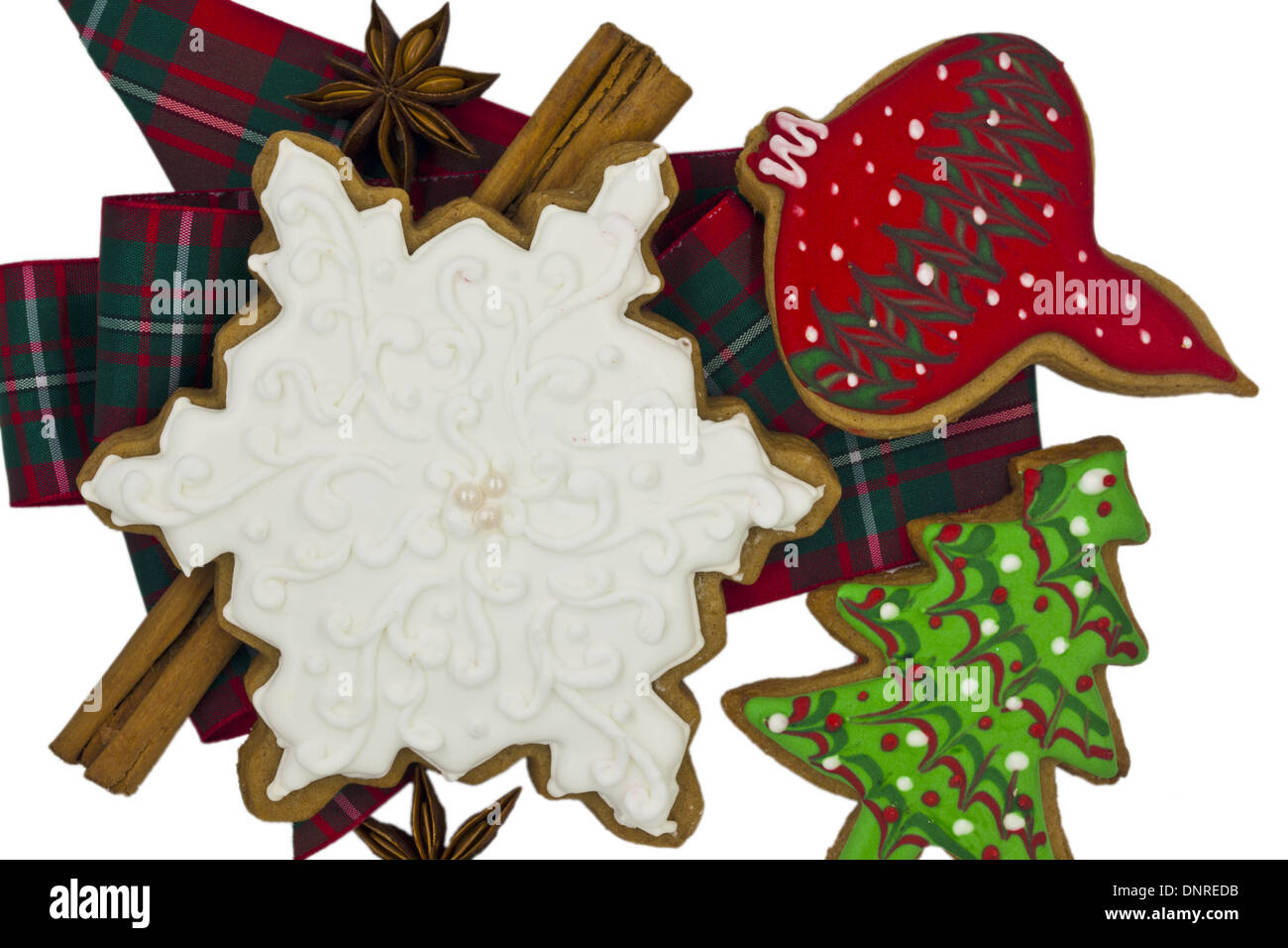 Iced cookies and spices with tartan ribbon isolated on white. - Stock Image