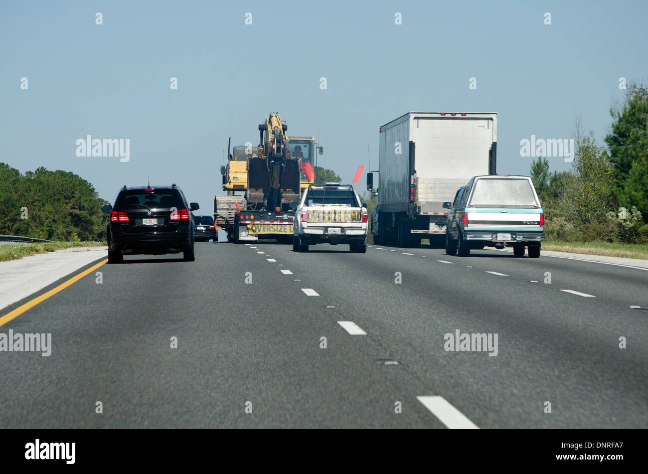 Escort vehicle truck with oversize load in center lane of highway America USA - Stock Image