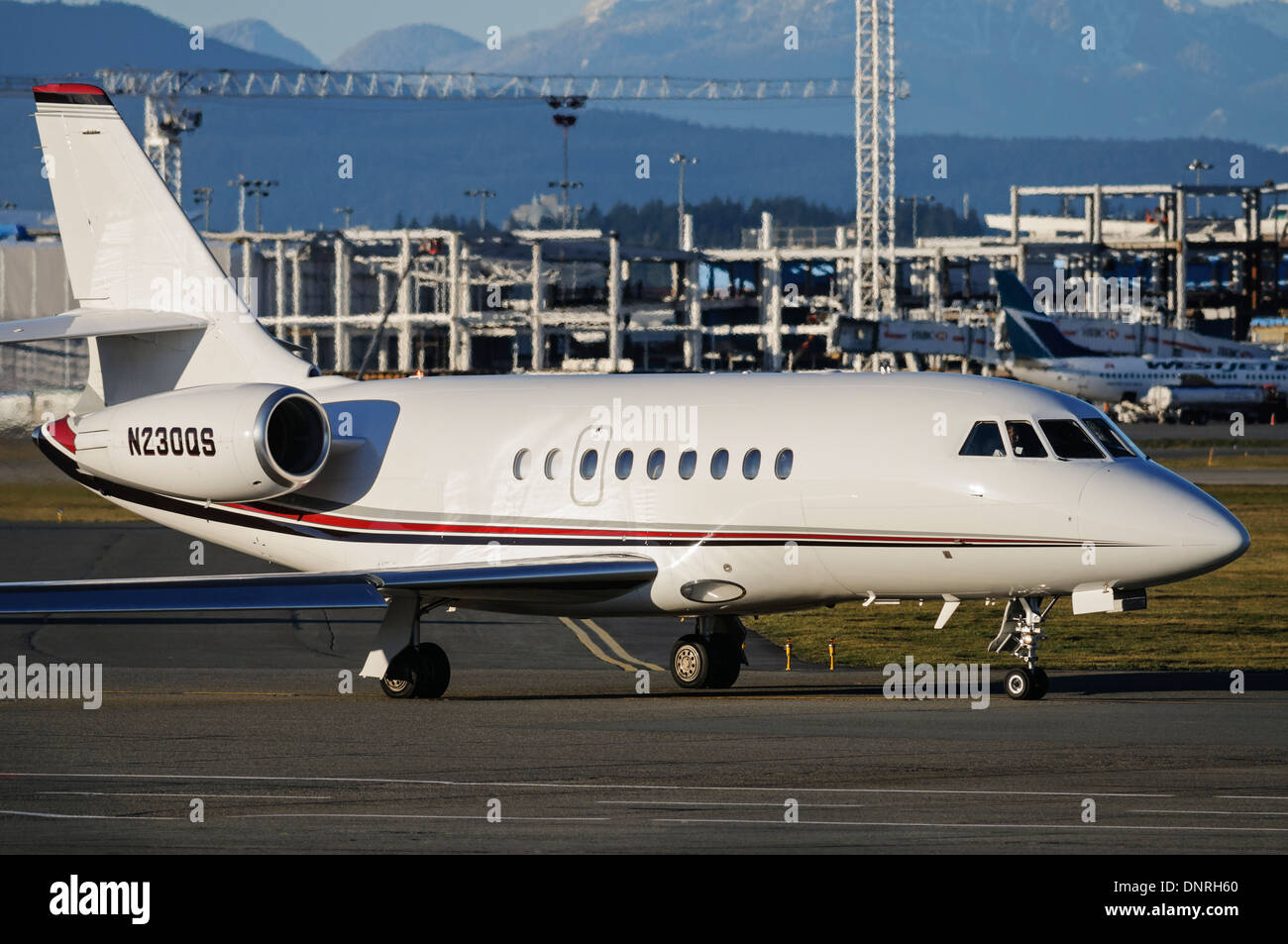 NetJets Dessault Falcon 2000EX EASy private executive business jet plane airplane taxies tarmac Vancouver International Airport - Stock Image